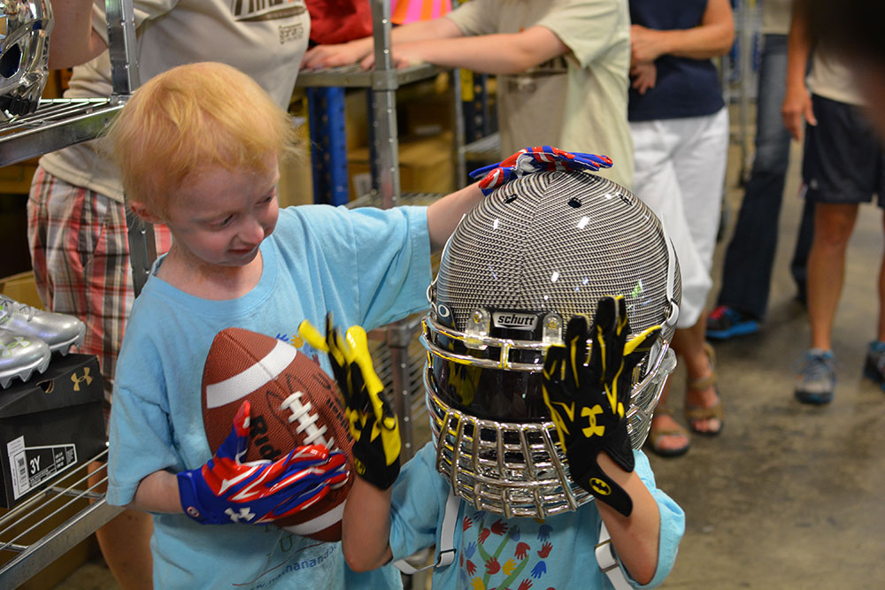 Bennett in a crazy football helmet while Nathan secures it